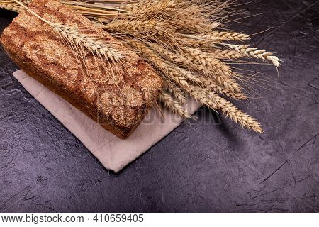 Loaf Of Whole Grain Bread And Shocks Of Wheat. Rustic Sourdough Bread With Crispy Crust. Rye Bread O
