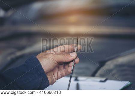 Car Mechanic Man Hand Checking Dipstick Engine Oil Car Mechanical On Site Service. Close Up Hand Man