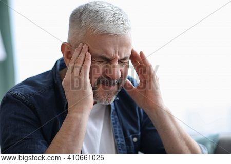 Closeup Of Mature Grey-haired Man Suffering From Headache At Home, Touching His Temples, Panorama Wi