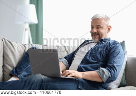 Happy Middle-aged Grey-haired Man Using Laptop While Resting On Sofa In Living Room, Empty Space. Ch