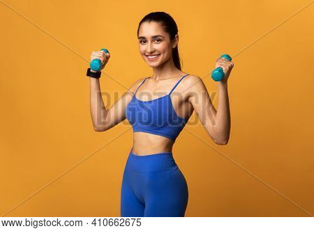 Biceps Exercises, Arms Workout. Portrait Of Happy Young Sportswoman Doing Training With Two Blue Dum
