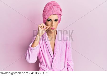 Young man wearing woman make up wearing shower towel on head and bathrobe mouth and lips shut as zip with fingers. secret and silent, taboo talking