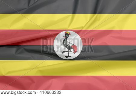 Fabric Flag Of Uganda. Crease Of Ugandan Flag Background, Black Yellow And Red ; A White Disc Depict