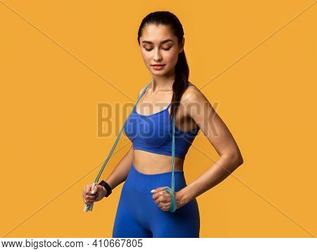 Fitness Instructor. Portrait Of Confident Young Woman In Blue Sports Bra And Leggings Holding Jump R