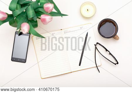 White Cozy Workplace With Notebook, Phone, Coffee, Flowers. Productive Lifestyle Backgound