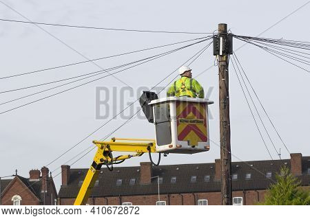 A Telecomms Power Engineer Working At Height On A Lift Platform To Gain Access To A Telegraph Pole