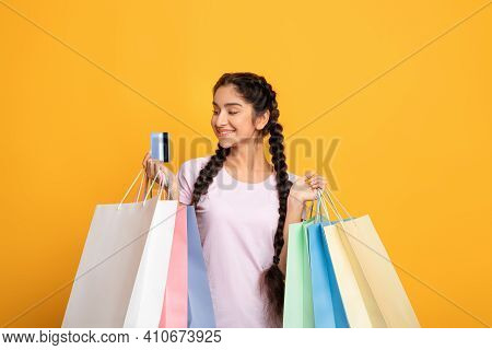 Time For Shopping. Portrait Of Smiling Young Indian Female Customer Holding Colorful Shopper Bags Wi