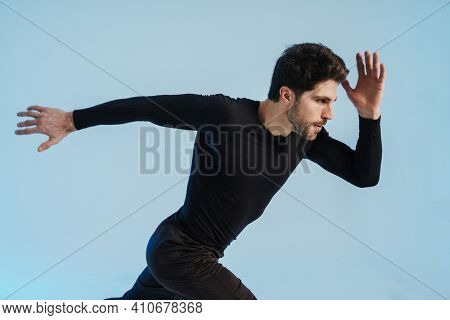 Young athletic sportsman running while working out isolated over blue background