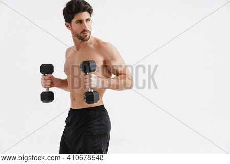 Half-naked athletic sportsman working out with dumbbells isolated over blue background