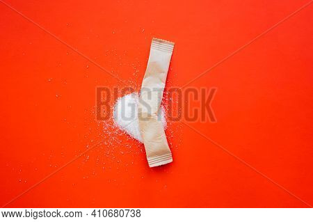 Broken Paper Stick With Spilled Sugar Against Vibrant Red Background. Abstract Product Photography,