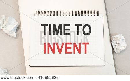 The Word Time To Invent Is Written In A Notebook That Sits On A Gray Desktop Along With A Laptop. Ac