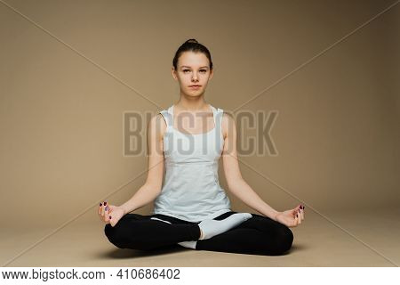 Beautiful Woman Meditating In Yoga Lotus Position. She Looks Peaceful, Calm And Zen. Consideration A