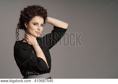 Portrait Of Cute Woman With Modern Hairdo In Stylish Clothes On Grey Background