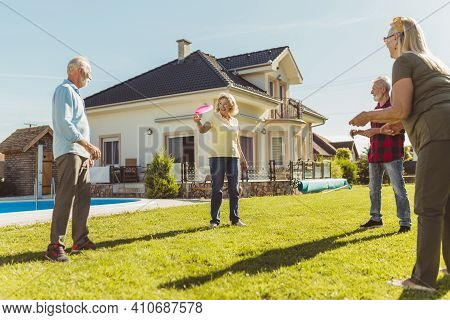 Group Of Active Senior People Having Fun Spending Sunny Summer Day Outdoors, Playing Catch And Toss