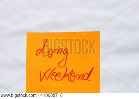 Long Weekend Handwriting Text Close Up Isolated On Orange Paper With Copy Space.