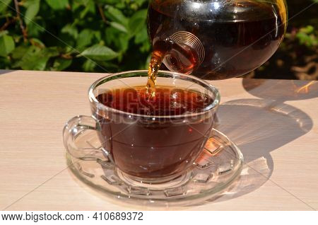 A Girl Pours Tea From A Transparent Teapot Into A Transparent Cup Against A Background Of Green Foli
