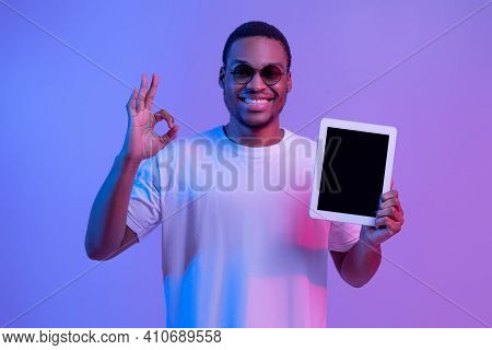 Happy African American Guy In Neon Lighting Holding Digital Tablet With Black Screen And Showing Ok