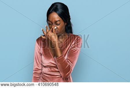 Young african american woman wearing sexy party dress smelling something stinky and disgusting, intolerable smell, holding breath with fingers on nose. bad smell