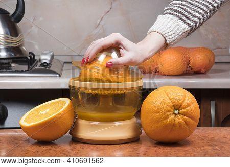 Closeup On Women's Hand Making Fresh Orange Juice. Female Hand Squeezing Orange Juice. Juicing Orang