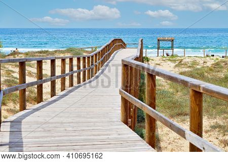 Wooden Empty Board Walk Leading Through Sand Dunes To Mediterranean Sea And Beach Of Los Arenales Ar