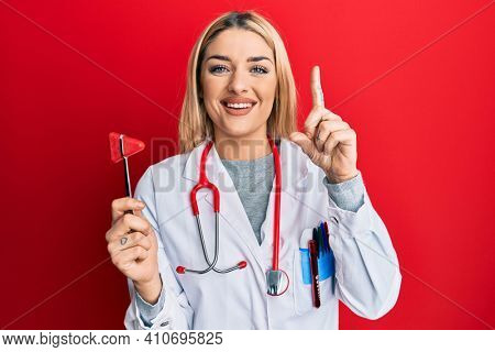 Young caucasian woman wearing doctor uniform holding medical reflex hammer smiling with an idea or question pointing finger with happy face, number one