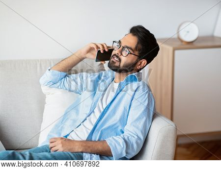Handsome Eastern Man Talking On Cellphone While Relaxing On Sofa At Home, Millennial Arab Guy Speaki