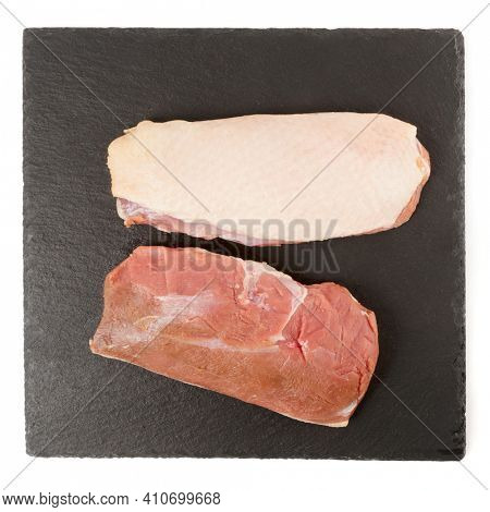 Duck fillets shot on black slate plate, isolated on white background