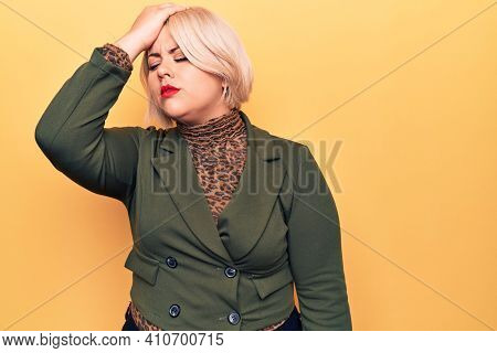 Young beautiful blonde plus size woman wearing elegant jacket over isolated yellow background surprised with hand on head for mistake, remember error. Forgot, bad memory concept.