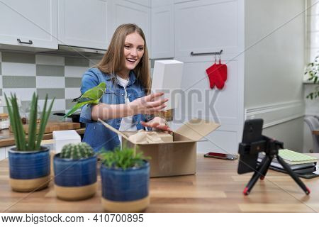 Woman Recording Video On Smartphone Moment Of Unpacking Cardboard Box. Showing Purchases Ordered On