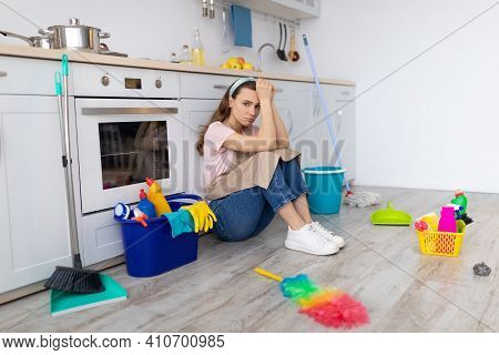 Housewife Depression. Sad Young Lady Feeling Trapped With Household Duties, Ready To Cry, Sitting On