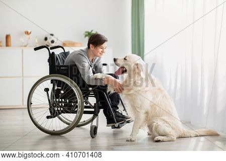 Happy Impaired Teenager Playing With His Dog At Home, Full Length Portrait. Cheerful Handicapped Ado