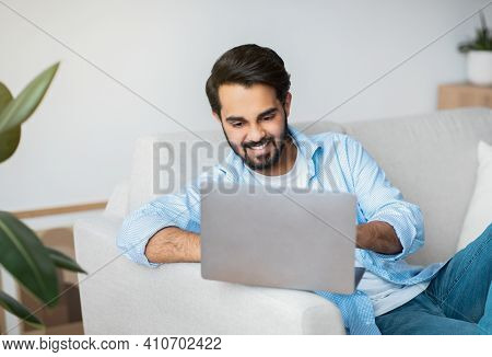 Online Job. Smiling Arab Freelancer Guy Using Laptop At Home, Handsome Eastern Man Sitting On Couch
