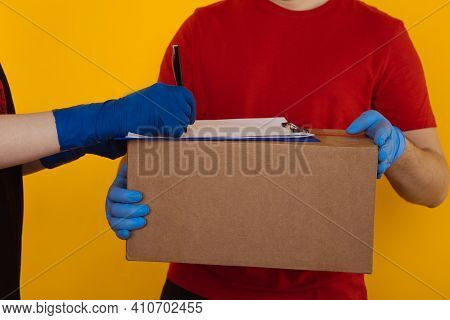 Delivery Man In The Red T-shurt And Gloves Holding An Empty Cardboard Box Isolated On Yellow Backgro