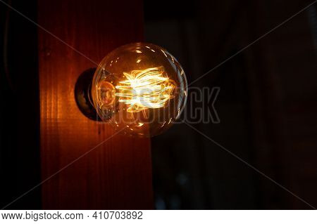 Old Glowing Light Bulbs On Dark Background.bright Glowing Clear Glass Lamp Pear Shaped Close Up. Vin