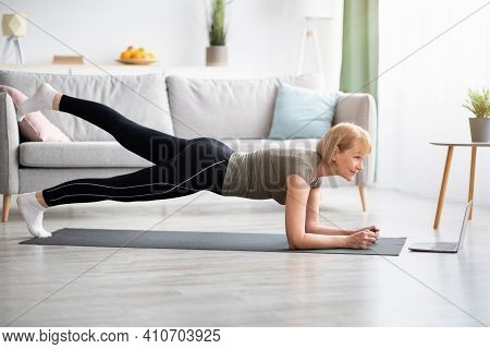Online Domestic Sports Concept. Mature Woman Exercising To Video On Laptop, Doing Elbow Plank At Hom