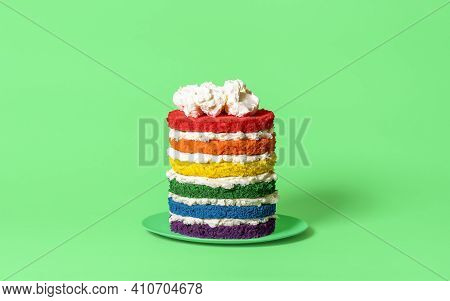 Birthday Cake With Six Colored Layers And Whipped Cream. Rainbow Cake Side View Against A Green Back