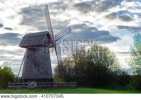Old Wooden Windmill On The Background Of A Gray Cloudy Sky On A Cloudy Day.