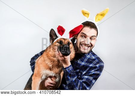 Caucasian Man With Yellow Rabbit Ears Hugs German Shepherd With Red Plush Ears. Creative Banner For
