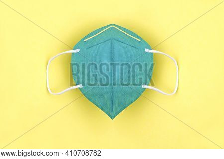 Green Ffp2 N95 Protective Face Mask On Yellow Background. Protection And Prevention Against Coronavi