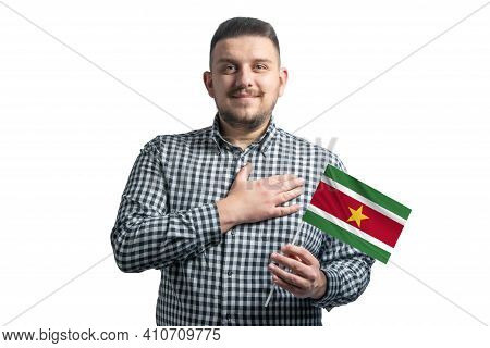 White Guy Holding A Flag Of Suriname And Holds His Hand On His Heart Isolated On A White Background