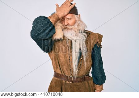 Old senior man with grey hair and long beard wearing viking traditional costume surprised with hand on head for mistake, remember error. forgot, bad memory concept.