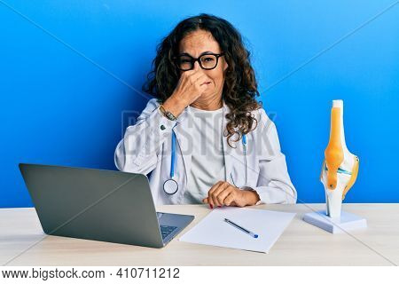 Beautiful middle age woman doctor at orthopedic clinic smelling something stinky and disgusting, intolerable smell, holding breath with fingers on nose. bad smell