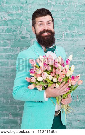 Romantic Gift. Macho Getting Ready Romantic Date. Tulips For Sweetheart. Man Well Groomed Wear Blue