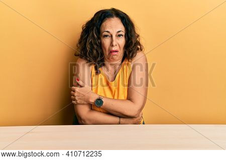 Beautiful middle age woman wearing casual clothes sitting on the table shaking and freezing for winter cold with sad and shock expression on face