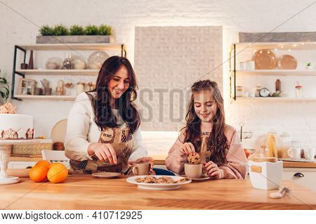 Mother's Day. Family Drinking Tea With Cookies At Home. Mother And Daughter Laughing Dipping Biscuit