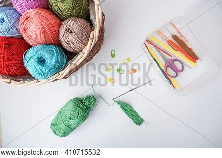 Crocheting. In The Photo, The Knitting Process, A Basket With Yarn, Yarn Scissors, Knitting Hooks An