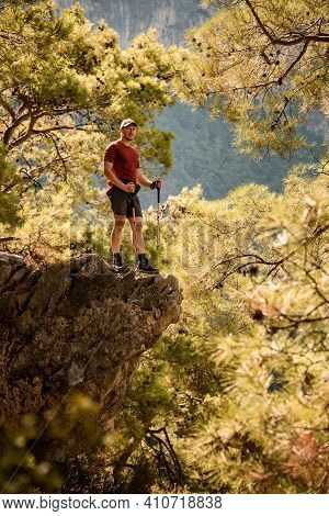 View Of Man Standing On Edge Of Cliff Surrounded By Green Pine Branches
