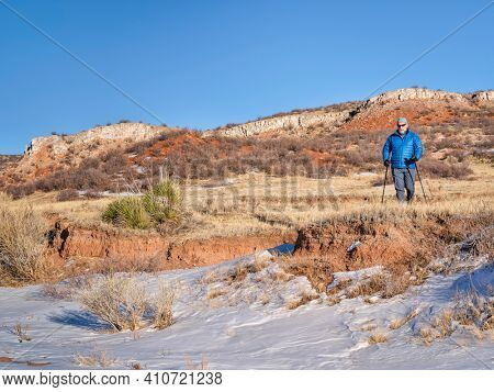 senior make is hiking with trekking poles at Colorado foothills of Rocky Mountains - Red Mountain Open Space, a popular hiking, biking and horse riding area near Fort Collins