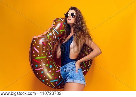 Side View Of Attractive Young Female In Swimwear, Trendy Sunglasses Holding Donut-shaped Swim Ring A