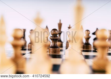 White And Black Wooden Pieces On A Chessboard. A Chessboard Set Up During A Game On A White Backgrou